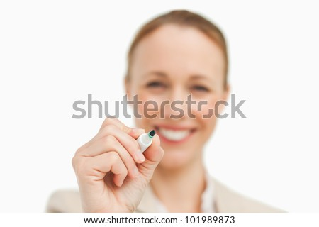Smiling businesswoman writing on a board against white background