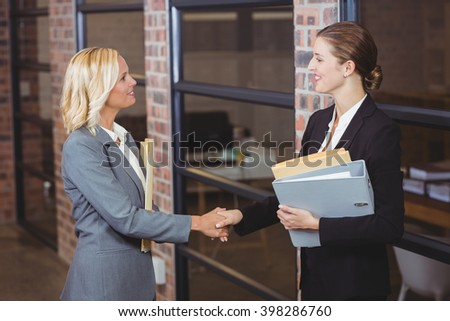Smiling businesswomen handshaking while standing at office - stock photo