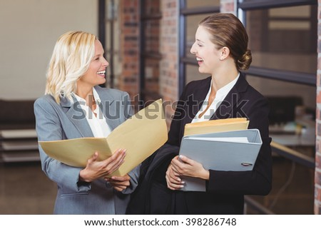 Smiling businesswomen holding documents while standing at office - stock photo