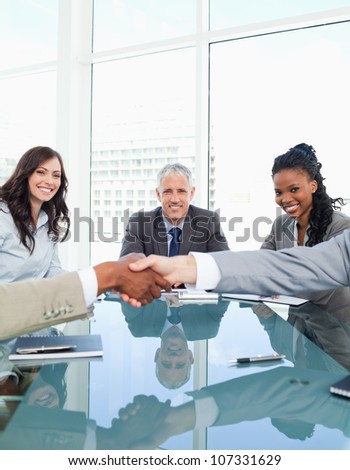 Smiling businesswomen in a meeting looking at co-workers shaking hands