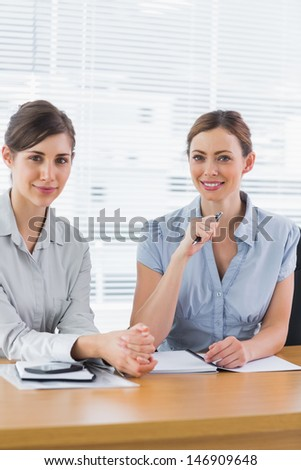 Smiling businesswomen working together and looking at camera at desk in office - stock photo