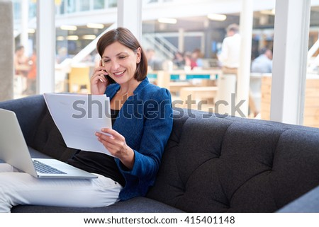 Smiling busineswoman on couch with phone, laptop and paperwork