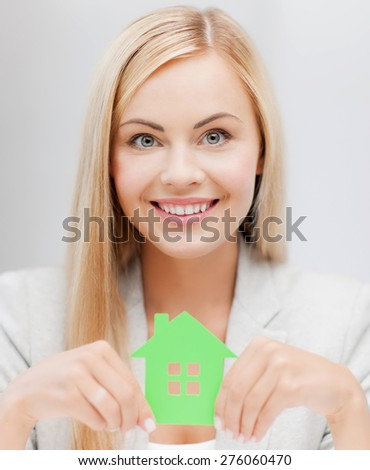 smiling busineswoman with green eco house symbol - stock photo