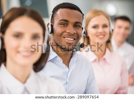 Smiling call center employees sitting in line with their headsets.