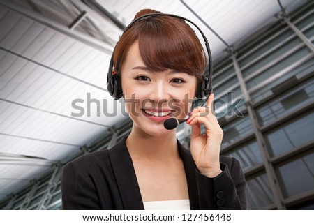 Smiling call center operator asian business woman in business background. - stock photo