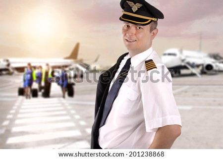 Smiling captain at the airport waiting for the crew - stock photo