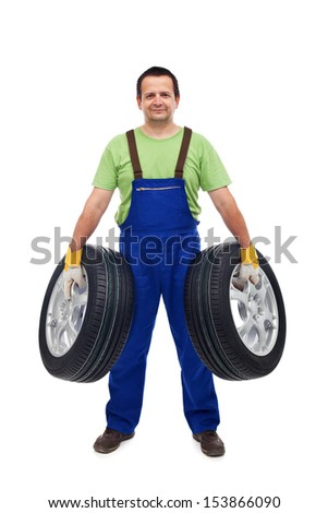 Smiling car mechanic holding two tires - isolated - stock photo
