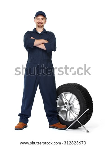 Smiling car mechanic with a tire isolated on white background. - stock photo