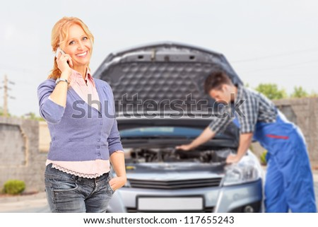 Smiling careless female talking on a mobile phone while in the background mechanic is checking her car