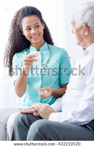 Smiling carer with stethoscope giving medicines to senior man.