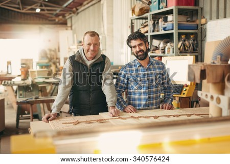 Smiling carpenters in front of their workbench - stock photo