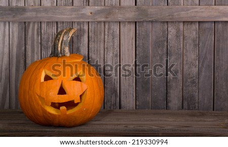 Smiling carved pumpkin on a wood floor with fence in background - stock photo