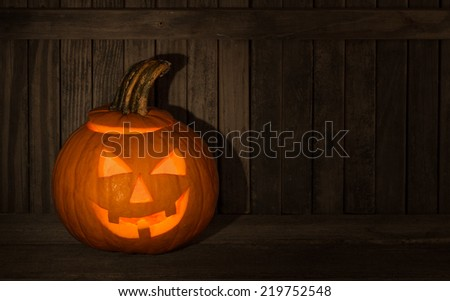 Smiling carved pumpkin with fence in background - stock photo