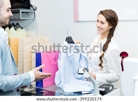 Smiling cashier and satisfied customer at checkout desk  - stock photo