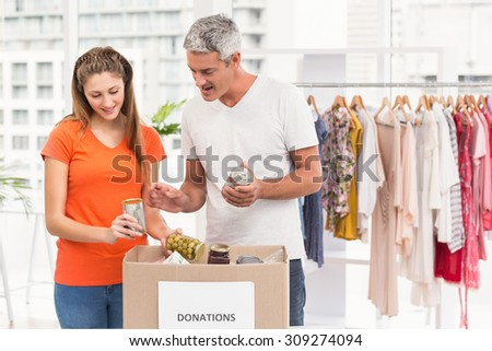 Smiling casual business colleagues sorting donations in the office - stock photo