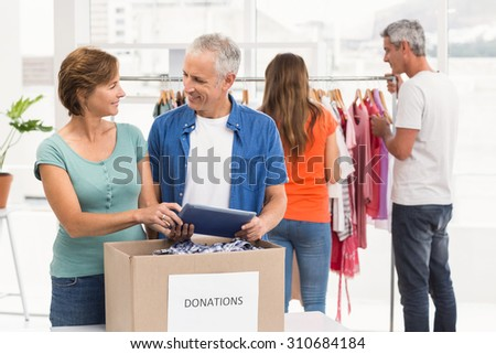 Smiling casual business colleagues with donation box in the office - stock photo