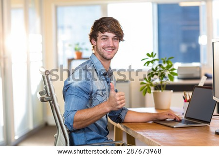 Smiling casual businessman sitting at desk in the office - stock photo