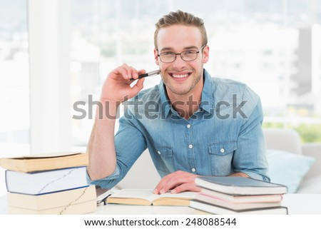 Smiling casual businessman studying at his desk in his office - stock photo