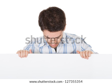 Smiling casual handsome young man holding up a blank white sign in front of his chest with copyspace for your text - stock photo