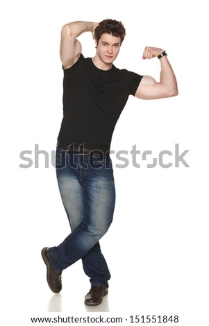 Smiling casual male in full length showing his muscles against white background - stock photo