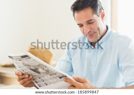 Smiling casual man reading newspaper in the kitchen at home