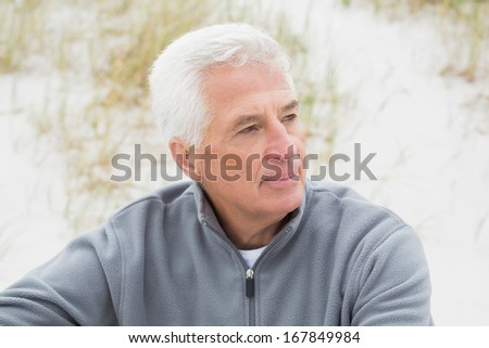 Smiling casual senior man relaxing on sand at the beach