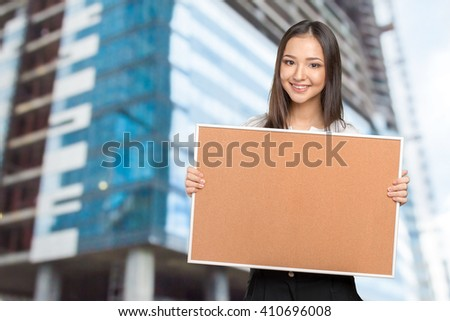 Smiling casual woman holding the empty cork board - stock photo