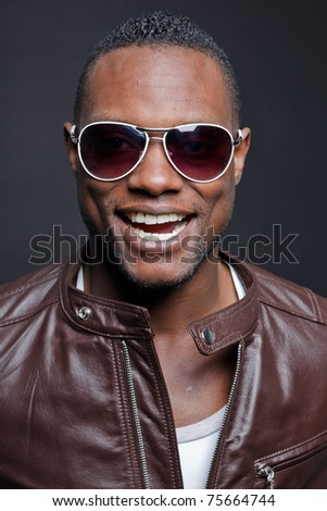 Smiling casual young black man wearing brown leather jacket and sunglasses. Studio portrait against dark background. - stock photo