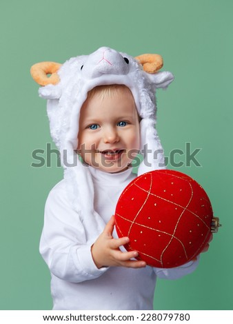 Smiling Caucasian baby with blue eyes wearing a sheep hat with yellow horns and white shirt standing on a green background holding red golden chinese ornament decoration, New Year 2015 concept, studio - stock photo