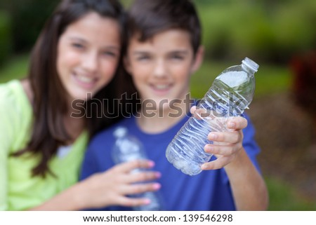 Smiling caucasian boy and girl holding up clear water bottles outside in yard, for recycling, with bottle in focus in foreground - stock photo