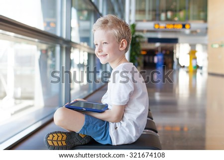 smiling caucasian boy with tablet sitting in the airport waiting for travel departure - stock photo