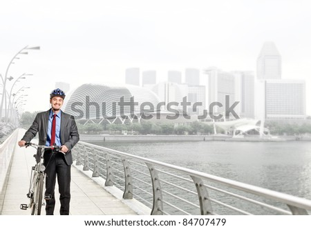 smiling caucasian businessman with his bike - stock photo