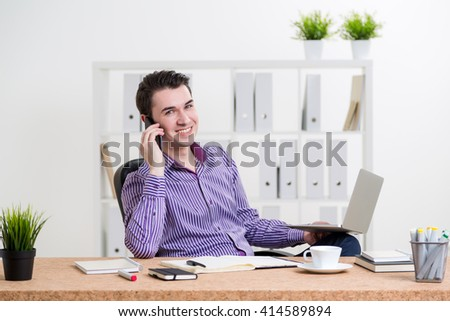Smiling caucasian businessperson in striped purple shirt sitting at office desk with laptop and other items and having a telephone conversation - stock photo