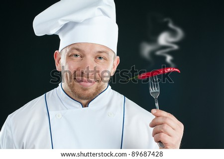 Smiling caucasian chef holding a fork with hot chili pepper, over a dark background - stock photo