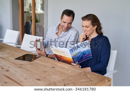 smiling Caucasian couple sitting at outdoor terrace patio having coffee and reading travel magazine