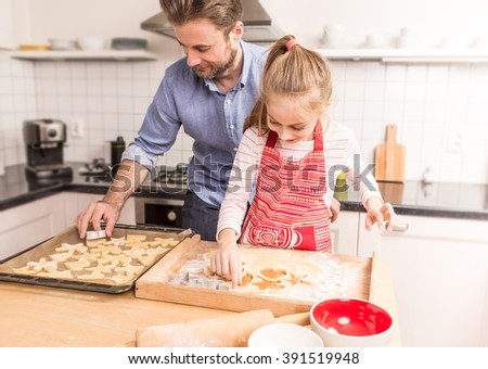 Smiling caucasian father and daughter having fun while preparing cookies to bake. Kitchen - happy family time.