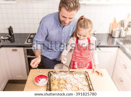 Smiling caucasian father and daughter sprinkling powdered sugar on homemade cookies. Baking - happy family time in the kitchen. - stock photo