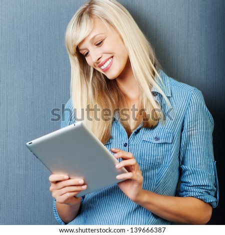 Smiling Caucasian female surfing using her tablet