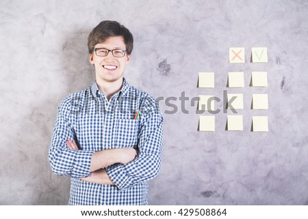 Smiling caucasian man with green and red pencils in shirt pocket standing next to concrete wall with cross and tick on stickers - stock photo