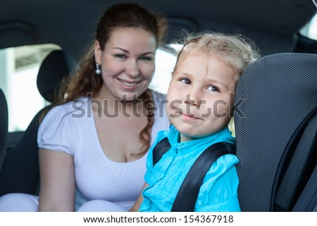 Smiling Caucasian mother with daughter sitting in car safety seat - stock photo