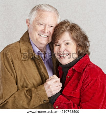 Smiling Caucasian older couple embracing and holding hands - stock photo