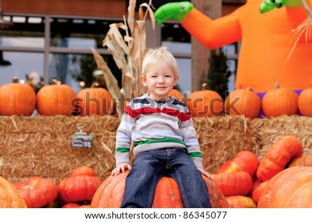 smiling caucasian toddler sitting on the huge pumpkin