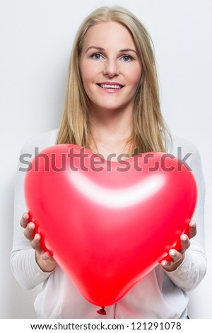 Smiling caucasian woman holding a red heart balloon - stock photo
