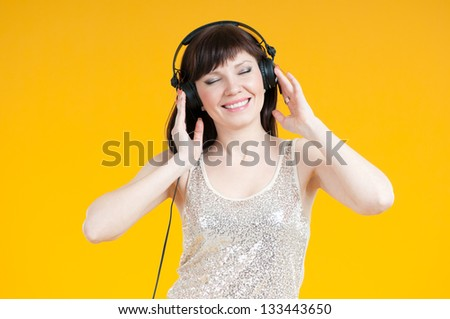Smiling caucasian woman listening to music in headphones, yellow background - stock photo