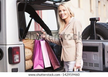 Smiling Caucasian woman putting her shopping bags into the car trunk. - stock photo