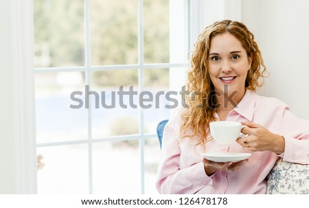 Smiling caucasian woman relaxing by window holding cup of coffee