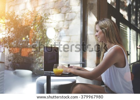 Smiling Caucasian woman rewriting in social network with friend via laptop computer while resting in cafe, young female developer creating program on net-book during work break in cozy restaurant - stock photo