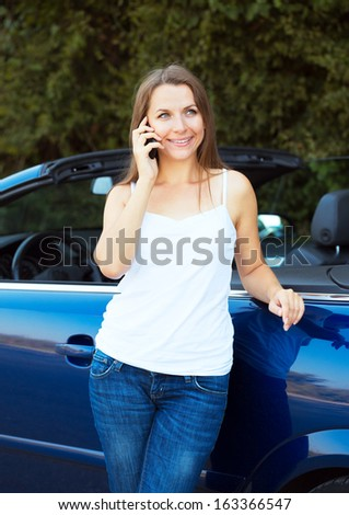 Smiling caucasian woman talking on phone in a cabriolet car