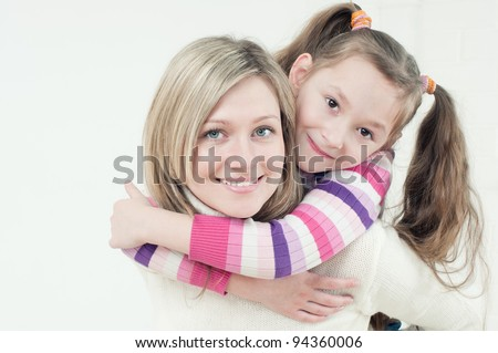Smiling caucasian young woman piggybacking her little daughter