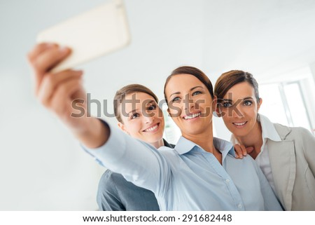 Smiling cheerful business women taking a selfie in the office using a smart phone - stock photo